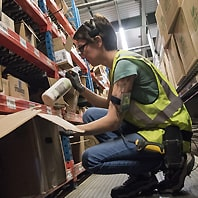 warehouse employee adding product to shipping box