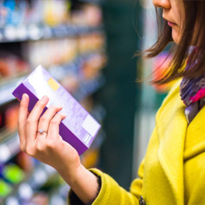 Woman examining ingredients on product from shelf
