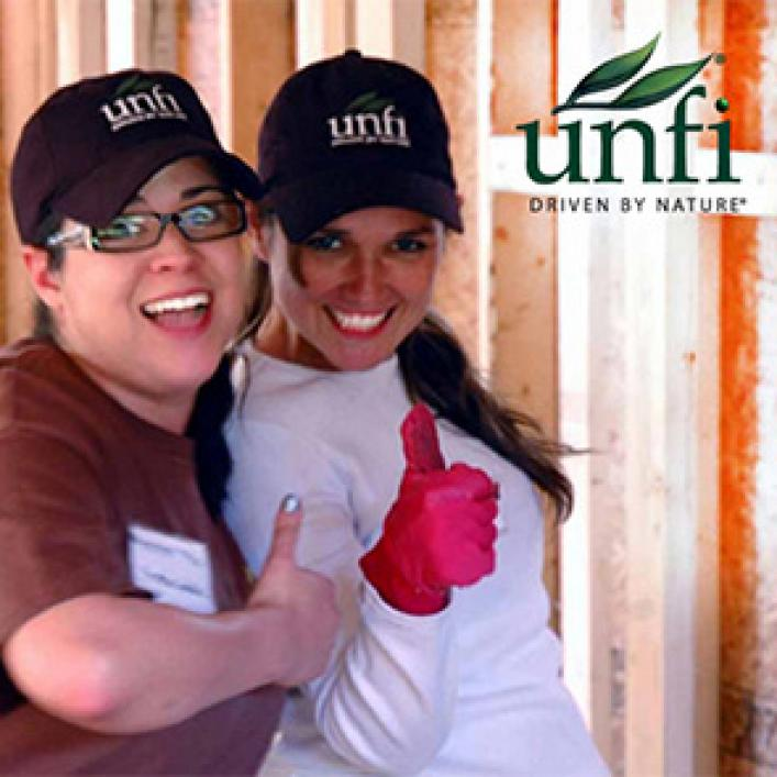 Happy UNFI employees giving thumbs up